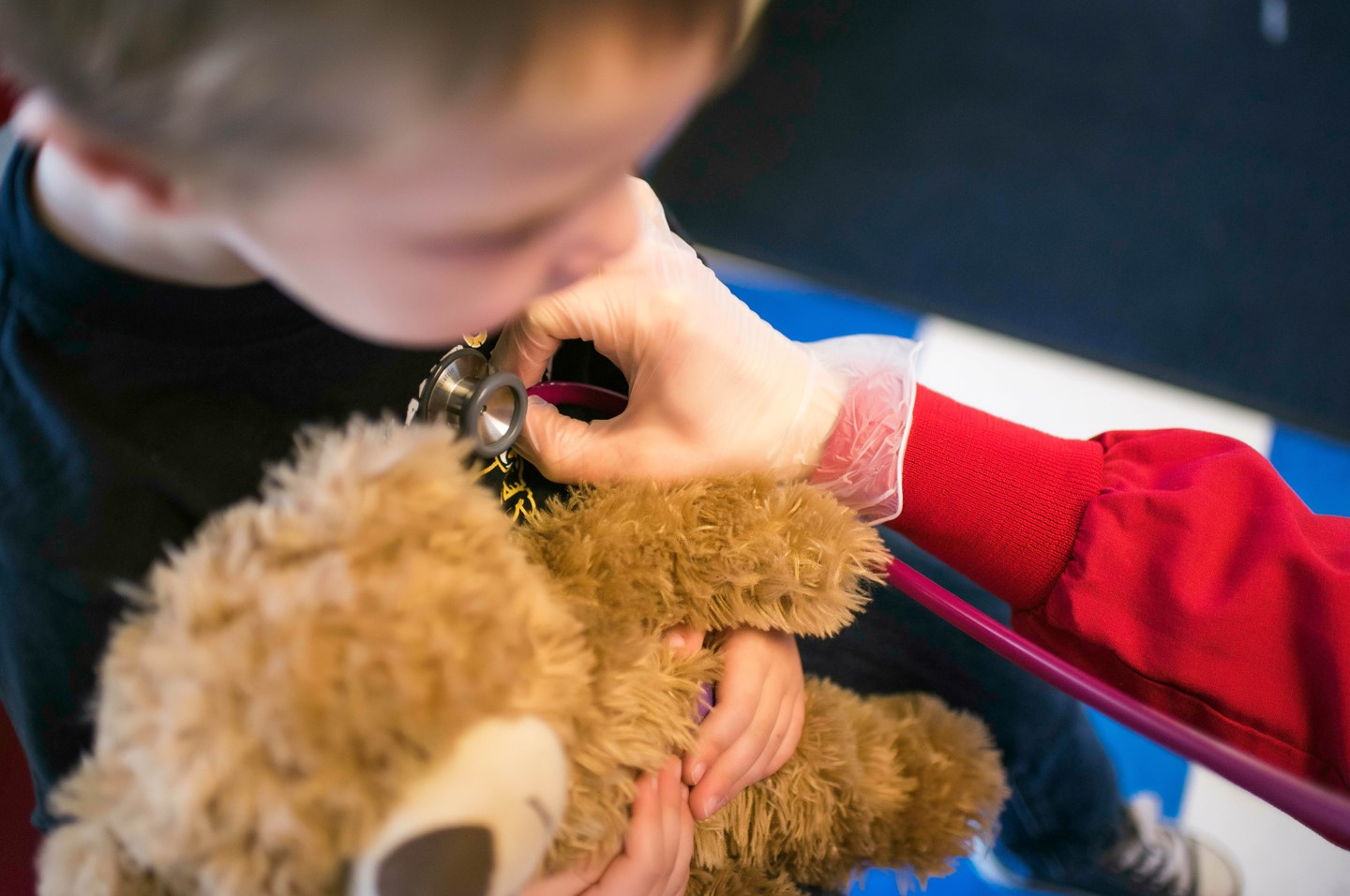 Kid holding teddy bear while a nurse listens to his chest with a stethoscope