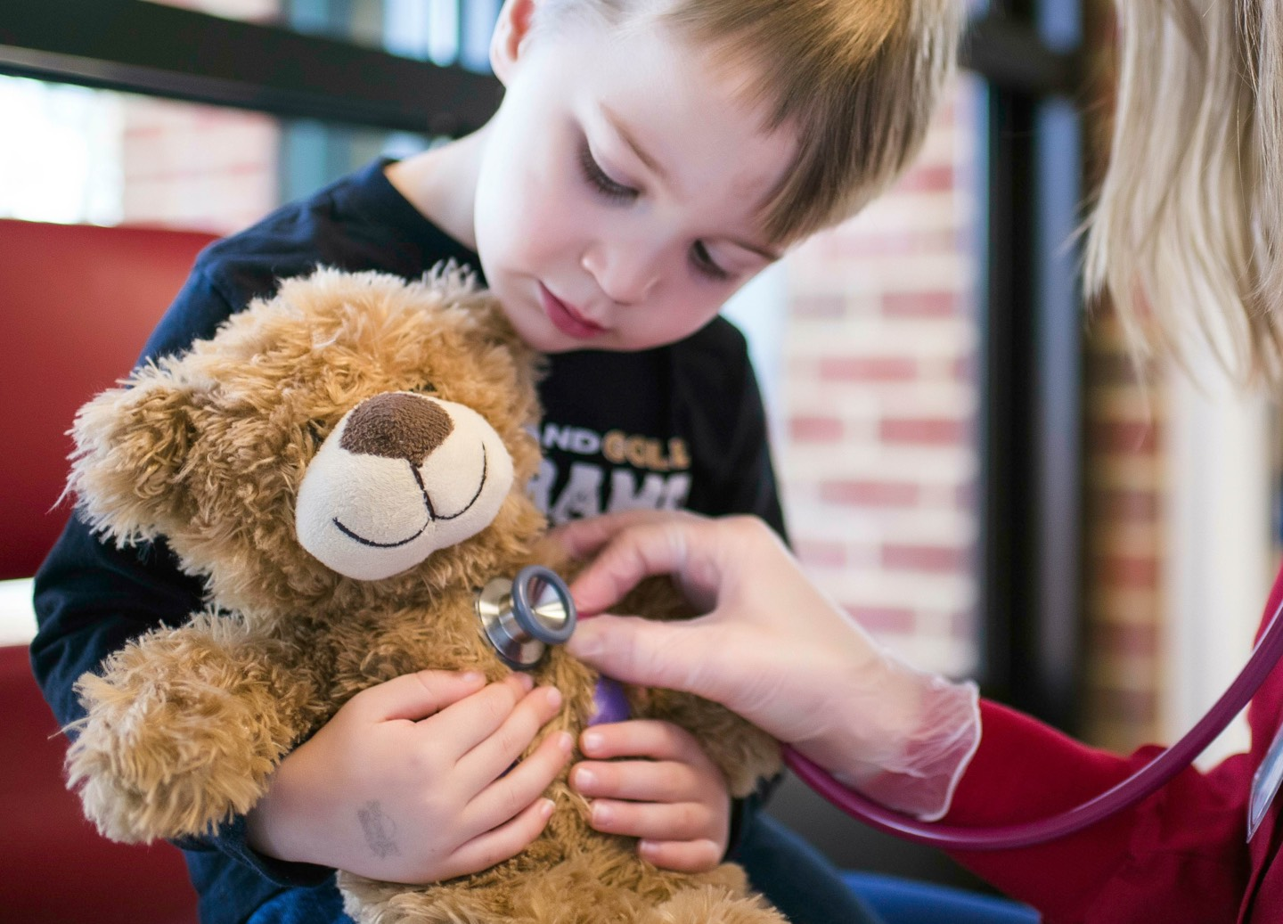 Student with teddy bear visits nurse for a checkup