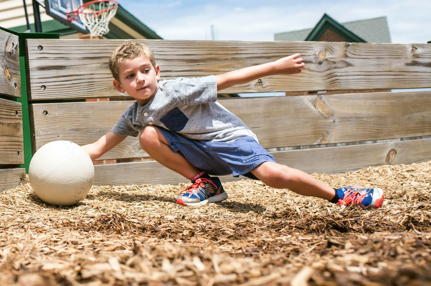 Boy grabbing ball in a mulched play-area