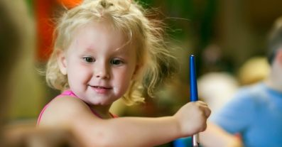 Preschool girl painting with blue paintbrush