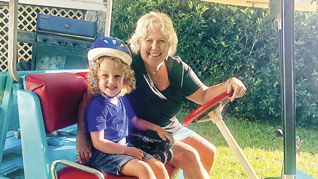 child in helmet on golf cart